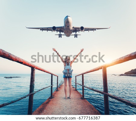 Airplane and woman at sunset. Summer landscape with girl standing on the sea pier with raised up arms and flying passenger airplane. Woman and landing commercial plane in the evening. Lifestyle #677716387