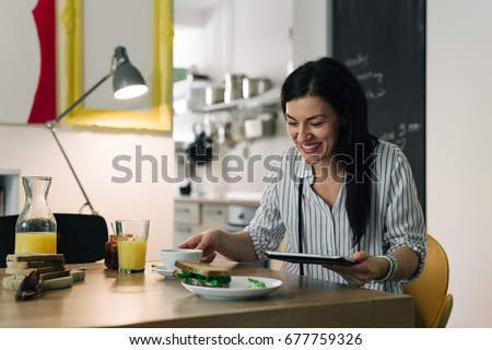 Online leisure time.young woman having breakfast while working on her tablet at home #677759326