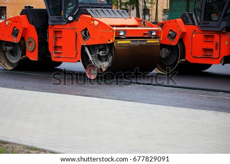 Two heavy compactor tires the upper layer of asphalt in the construction of a parking lot for tourist buses. #677829091