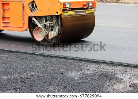 Heavy compactor tires the upper layer of asphalt in the construction of a parking lot for tourist buses. #677829094