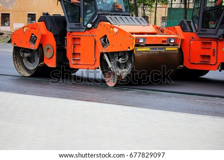 Two heavy compactor tires the upper layer of asphalt in the construction of a parking lot for tourist buses. #677829097