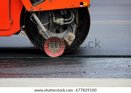 Heavy compactor tires the upper layer of asphalt in the construction of a parking lot for tourist buses. #677829100