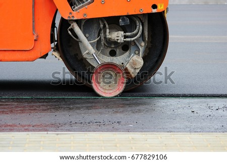 Heavy compactor tires the upper layer of asphalt in the construction of a parking lot for tourist buses. #677829106