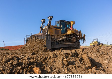 Construction Earthworks Dozer Excavator  Construction industrial earthworks dozer excavator  machine bucket pushing sand stones closeup abstract. #677853736