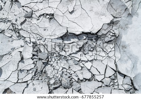 Cracked concrete texture background. Grey surface with cracks close up. A lot of pieces of splintered plaster. Abstract concept of split, dissent, disagreement, discord. Sunny day with shadows. Royalty-Free Stock Photo #677855257