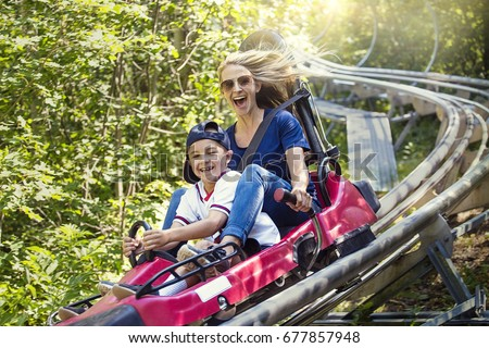 Smiling women and her boy riding downhill together on an outdoor roller coaster on a warm summer day. She has a fun expression as they enjoy a thrilling ride on a red amusement park ride Royalty-Free Stock Photo #677857948
