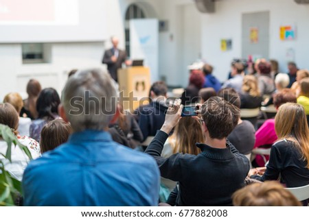 Male speaker giving presentation in lecture hall at university workshop. Audience in conference hall. Rear view of unrecognized participant in audience. Scientific conference event. #677882008