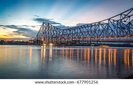 Howrah bridge - The historic cantilever bridge on the river Hooghly with twilight sky. Howrah bridge is considered as the busiest bridge in India. #677901256