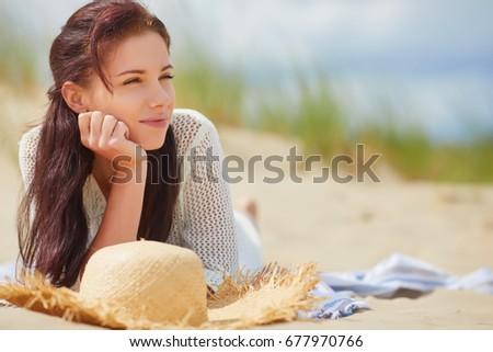 Brunette woman  lies on the sand on an empty beach #677970766