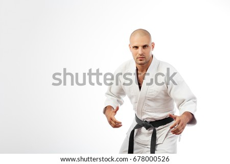 Young man fighter in white kimono with black belt for judo, jujitsu posing in combat pose on isolated white background Royalty-Free Stock Photo #678000526