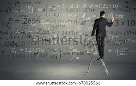 A businessman in elegant suit standing on a small ladder and writing numbers, calculating on grey wall background #678025561