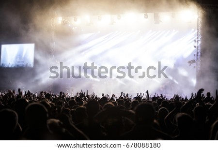 Photo of many people enjoying rock concert, crowd with raised up hands dancing in nightclub, audience applauding to musician band, night entertainment, music festival, happy youth, luxury party #678088180