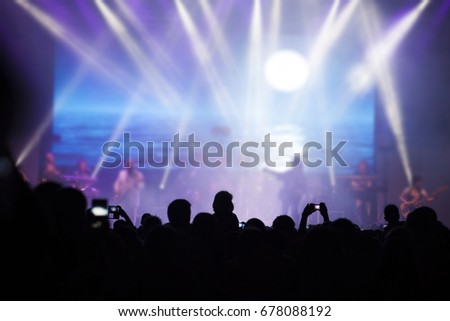 Photo of many people enjoying rock concert, crowd with raised up hands dancing in nightclub, audience applauding to musician band, night entertainment, music festival, happy youth, luxury party #678088192