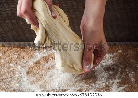 Hands prepare dough on a dark background #678152536