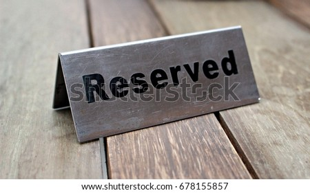 Reserved Table. A tag of reservation placed on the wood table. Reserved logo. Reservation sign. Metal tag with reservation logo. Reserved table in a restaurant. Hungry. Royalty-Free Stock Photo #678155857