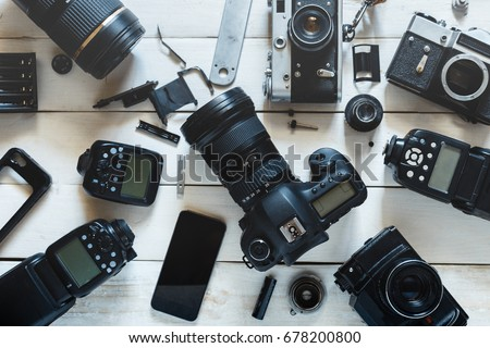 Vintage Film Camera, Digital Camera And Smartphone On White Wooden Background Technology Development Concept. Top View Royalty-Free Stock Photo #678200800