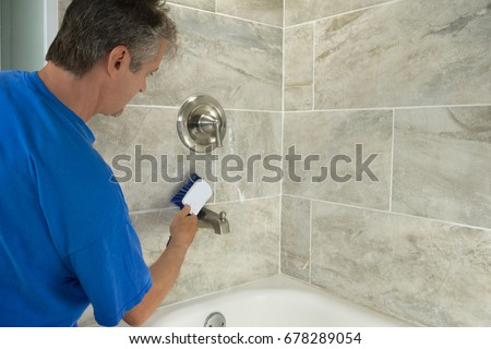 A man doing household chores is cleaning bathroom bathtub tiles and fixtures with a soapy white scrub brush. #678289054