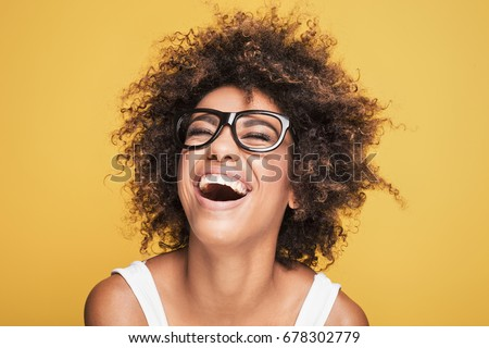 Young beautiful african american girl with an afro hairstyle. Attractive girl wearing eyeglasses. Portrait. Yellow background.  Royalty-Free Stock Photo #678302779