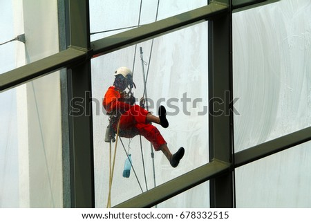 Men or women attached as a climber and cleaning a glass window on a high and dangerous structure #678332515