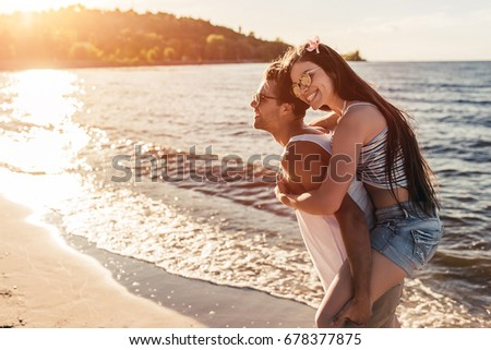 Young beautiful couple is having fun on beach and smiling. #678377875