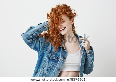 Happy beautiful girl smiling with closed eyes touching her red curly hair over white background. Royalty-Free Stock Photo #678396601