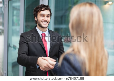 Young smiling business people shaking hands #678407188