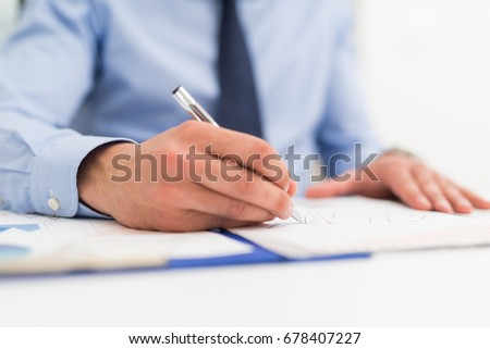 Detail of a businessman writing on a document #678407227