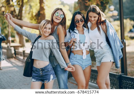 Four beautiful girls in stylish clothes in summer city #678415774