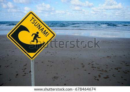 "Yellow sign ""Tsunami warning"" on Sea beach background"