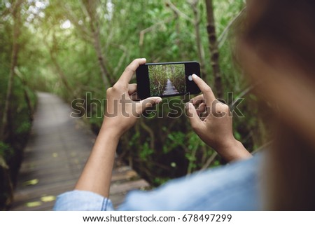 woman use phone taking nature photo