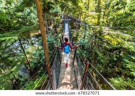 Canada travel tourist woman walking in famous attraction Capilano Suspension Bridge in North Vancouver, British Columbia, canadian vacation destination for tourism. #678527071