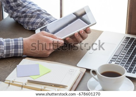 Young man working in an office and using tablet pc #678601270