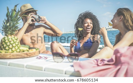 Happy friends having fun and eating fresh pineapple fruit at boat party - Young people taking photos in caribbean sea tour - Youth, tropical, travel and summer vacation concept - Focus on black girl #678605134