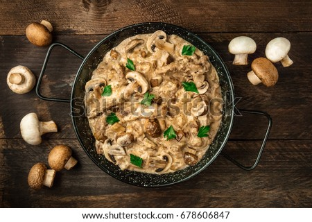 Mushroom beef stroganoff, with cremini and champignons, in a frying pan, shot from above on a dark rustic texture with a place for text #678606847