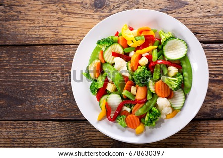 plate of stir fry vegetables on wooden table, top view #678630397