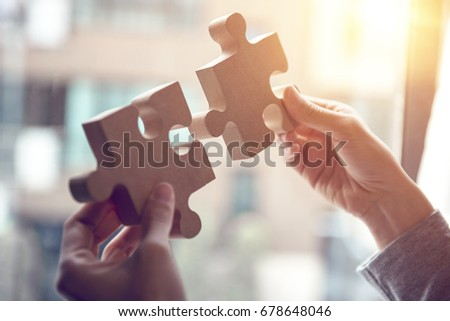 Closeup hand of woman connecting jigsaw puzzle with sunlight effect, Business solutions, success and strategy concept Royalty-Free Stock Photo #678648046