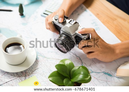 Capture planning map for traveling on wooden table with coffee cup and plant #678671401