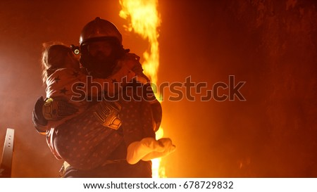 Brave Fireman Holds Saved Girl in His Arms in a Burning Building with open fire in the Background.