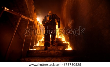 Strong and brave Firefighter Going Up The Stairs in Burning Building. Stairs Burn With Open Flames. #678730525