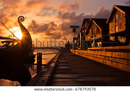 Seafront on the sunset with Viking ship #678793078