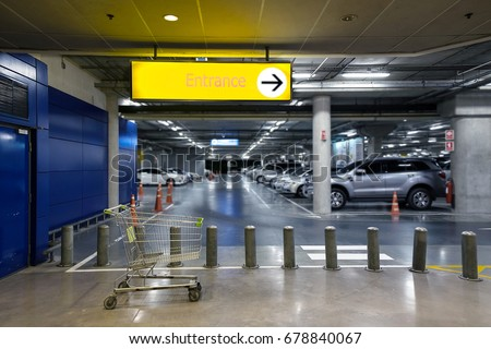 Entrance signboard with direction arrow and a cart is foreground in parking garage