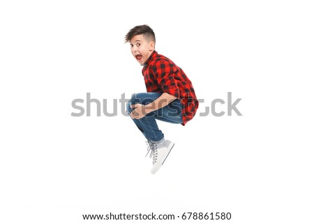 Side view of excited young boy jumping isolated on white.  Royalty-Free Stock Photo #678861580