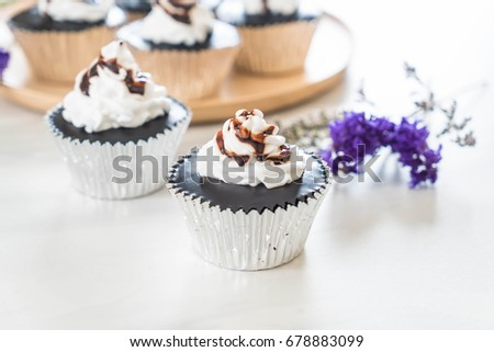 chocolate cup cake with whipped cream on table #678883099