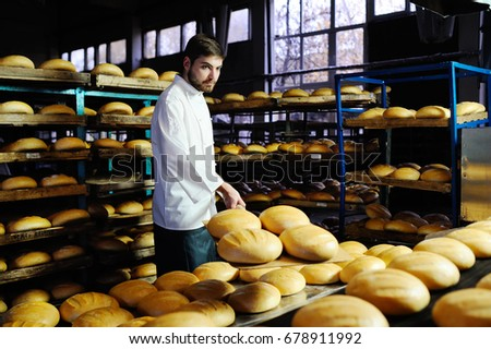 young cute baker smiling pulls out of the oven fresh bread shovel bread #678911992