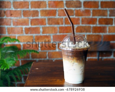 A plastic glass of iced coffee latte; upper layer is brown bitter coffee lower is fresh milk, brick background with selective focus. #678926938