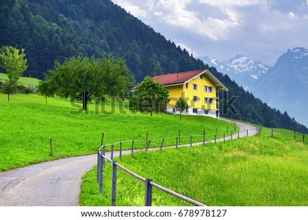 Beautiful view of idyllic mountain scenery in the Alps with traditional chalet with green alpine meadows and snow covered mountain peak in Uri canton nearby Altdorf, Switzerland #678978127