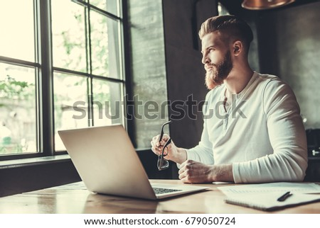 Young bearded man in glasses using a laptop while working in the office #679050724
