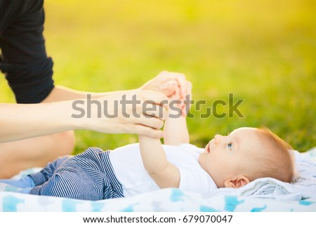 Mother playing with her baby boy outdoors.  #679070047