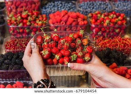 Buying berries in the local market. Close-up, hand touches strawberry. Various berries in the background. #679104454