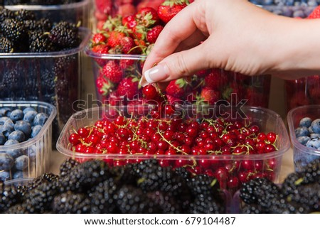 Buying berries in the local market. Close-up, hand touches currant. Various berries in the background. #679104487
